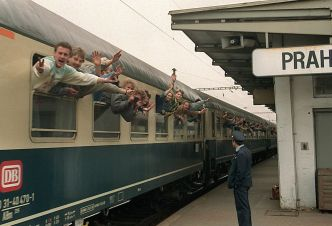 East-German refugees wave to newsmen as they leave